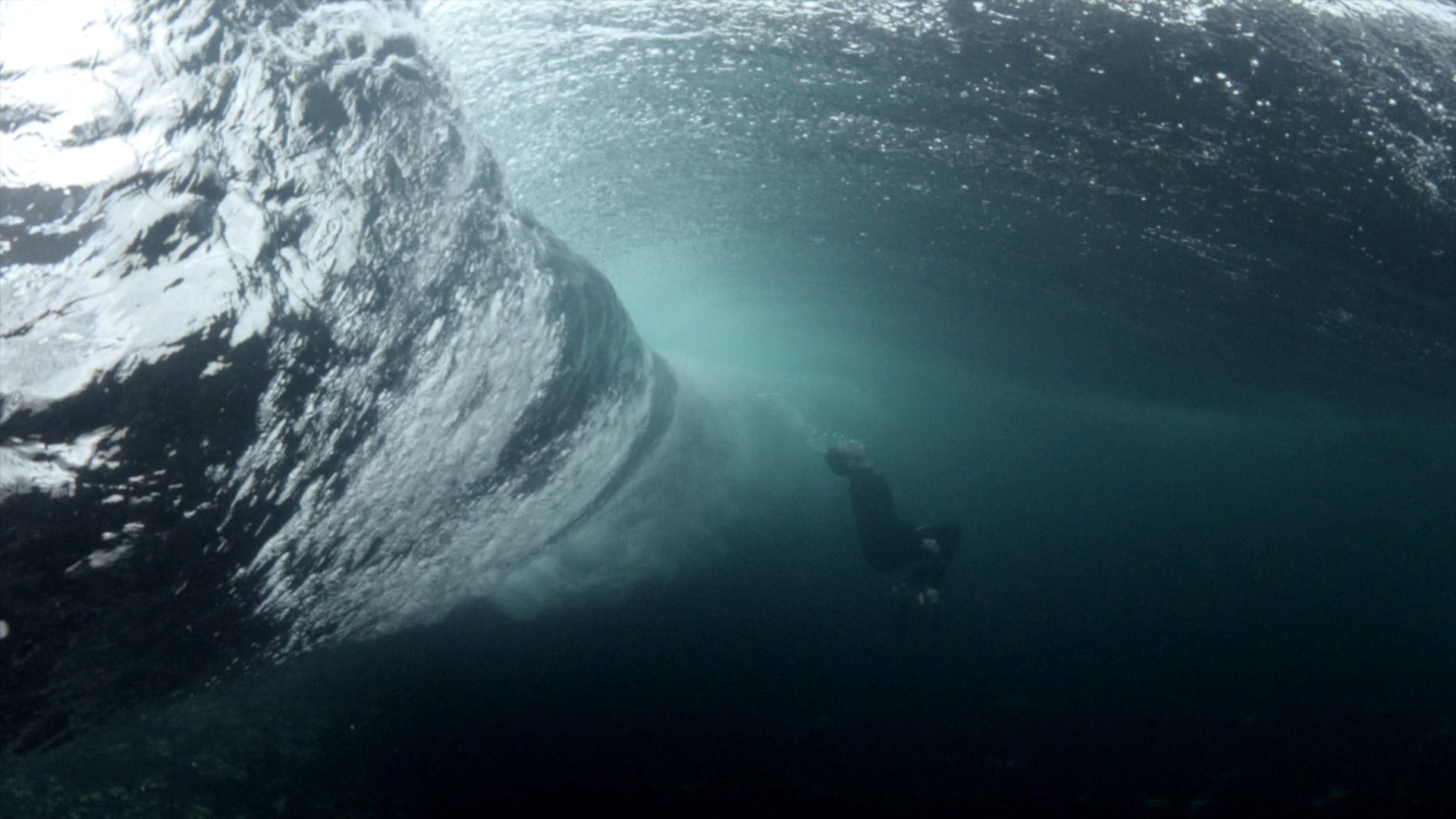 Underwater shot of a man ducking under a heavy barrelling wave in clear water