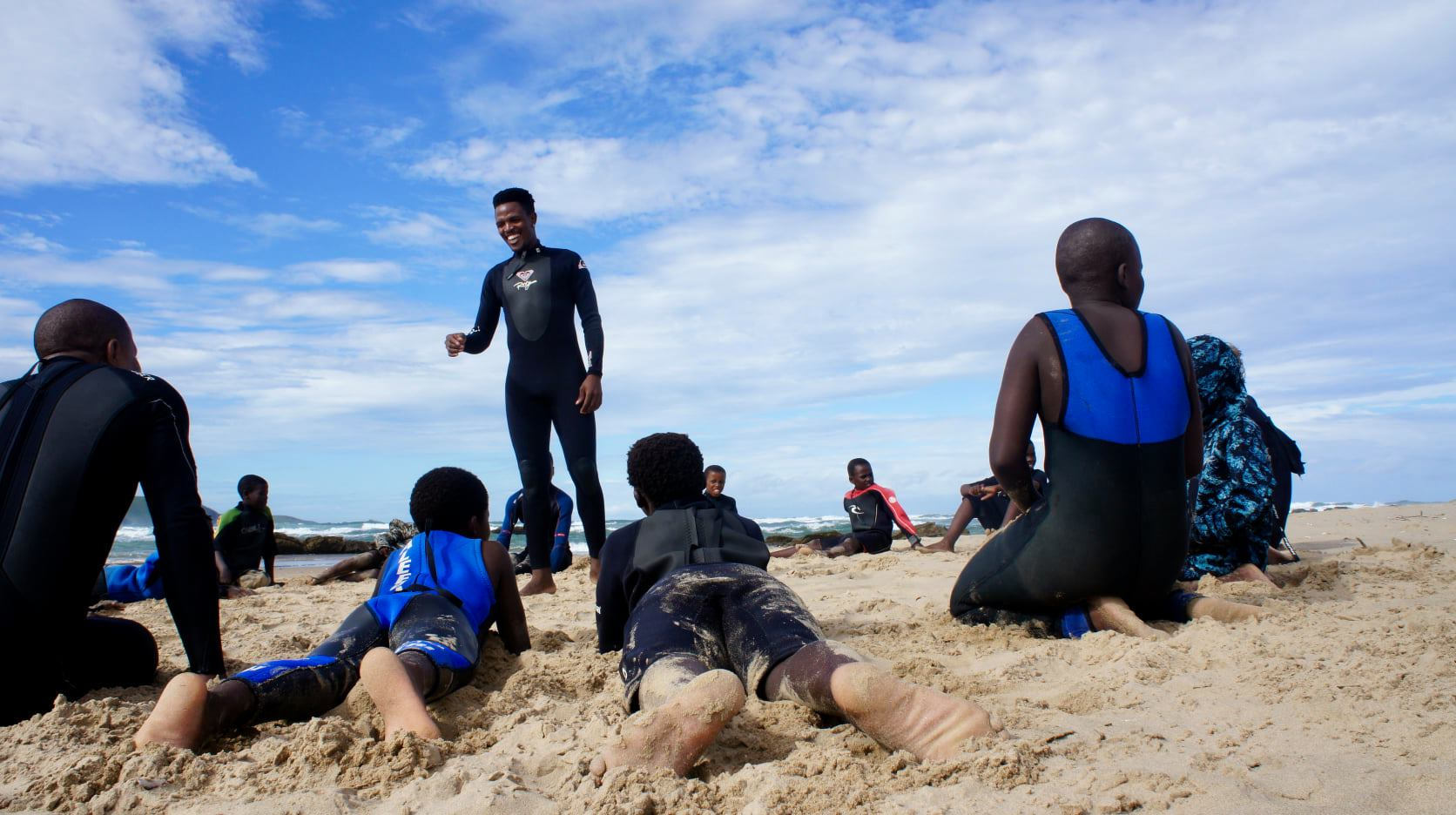 Group of children sit in a circle around their surf instructor while attending Thatha iLiza