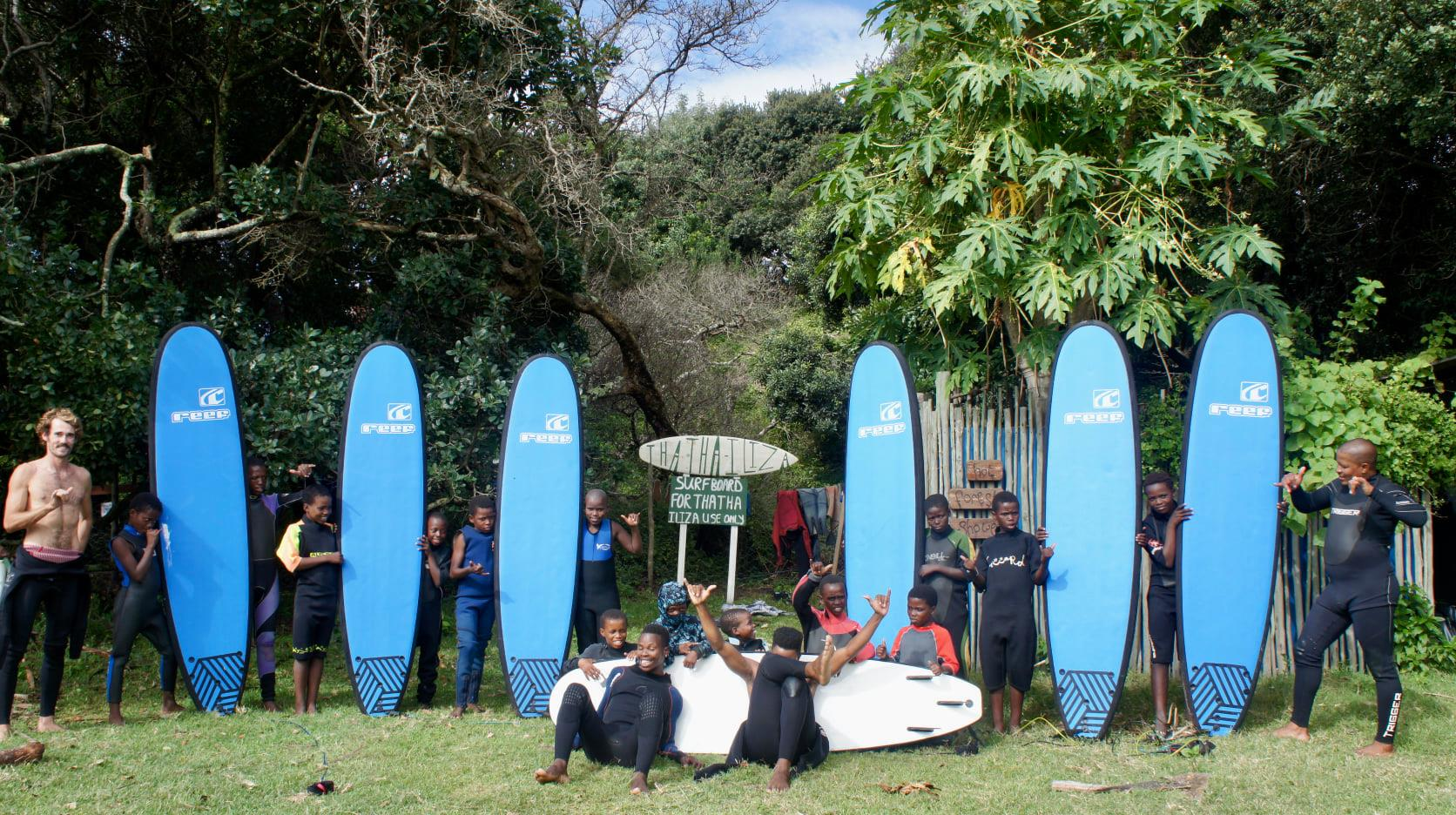 Thatha iLiza team in wetsuits holding surfboards
