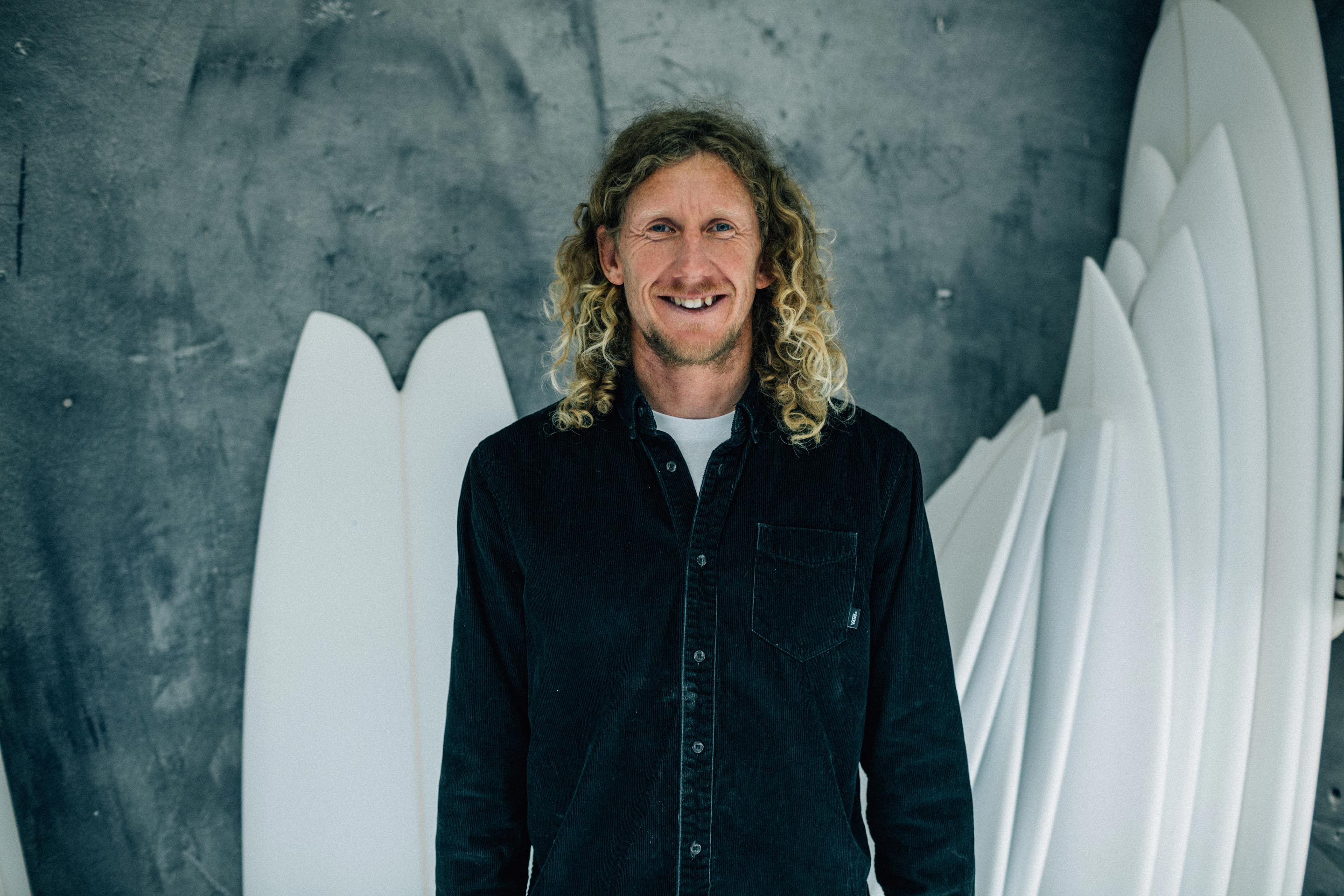 Vans + Finisterre editorial - James Parry in his workshop standing in front of some of his own boards