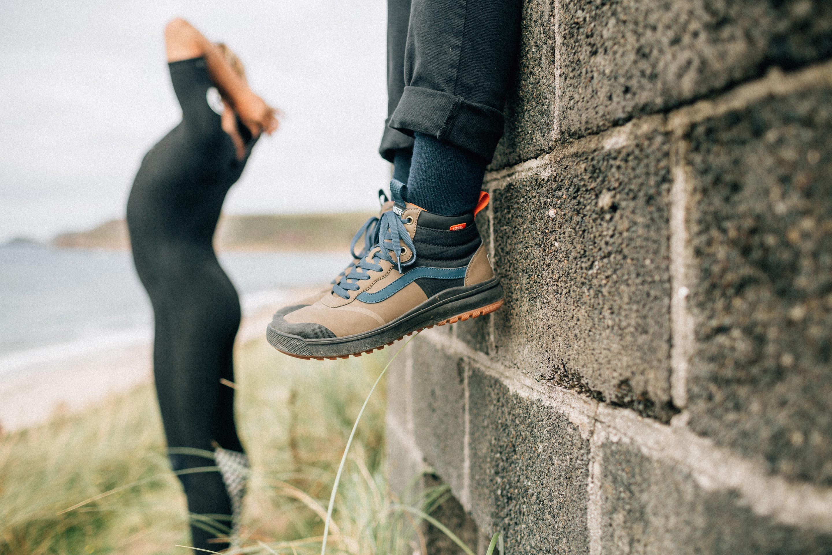 Vans + Finisterre editorial -  Seb Smart gets suited up while Paige Maddisons legs dnagle from the wall, wearing the new vans + Finisterre ultrarange hi dl lightweight walking boots