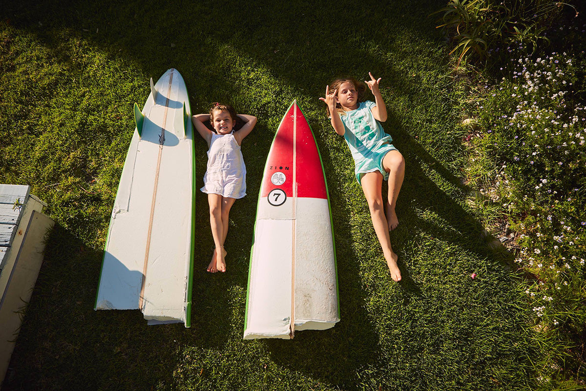 The author's young daughters lie next to a snapped big wave gun