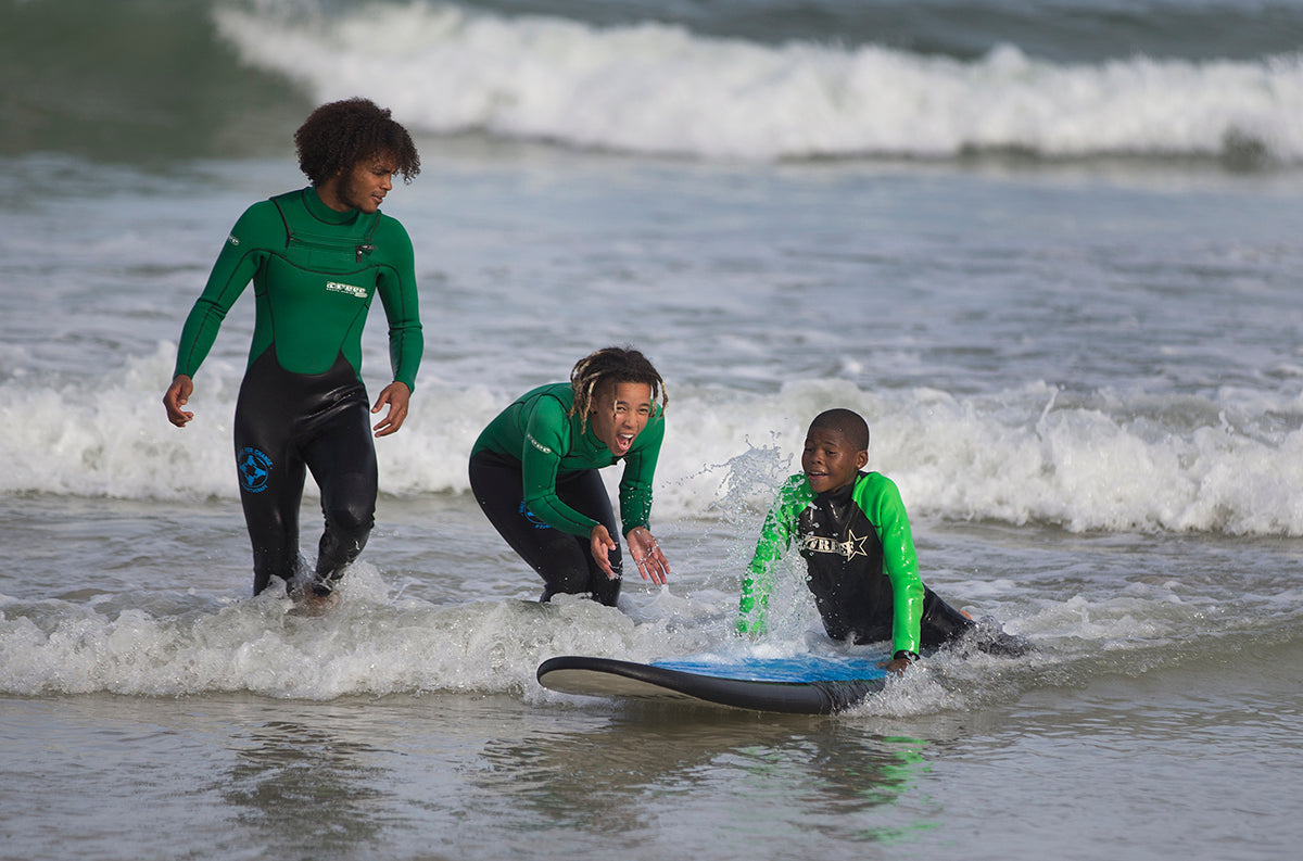 Two Waves For Change instructors helping a child catch a small white water wave