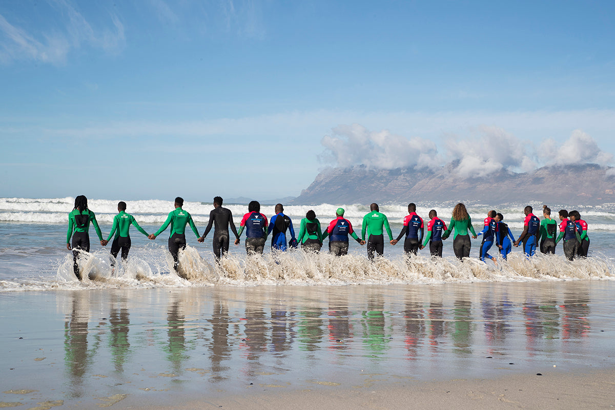 A group hold hands in the sea as part of a surf therapy session by Waves for Change in South Africa