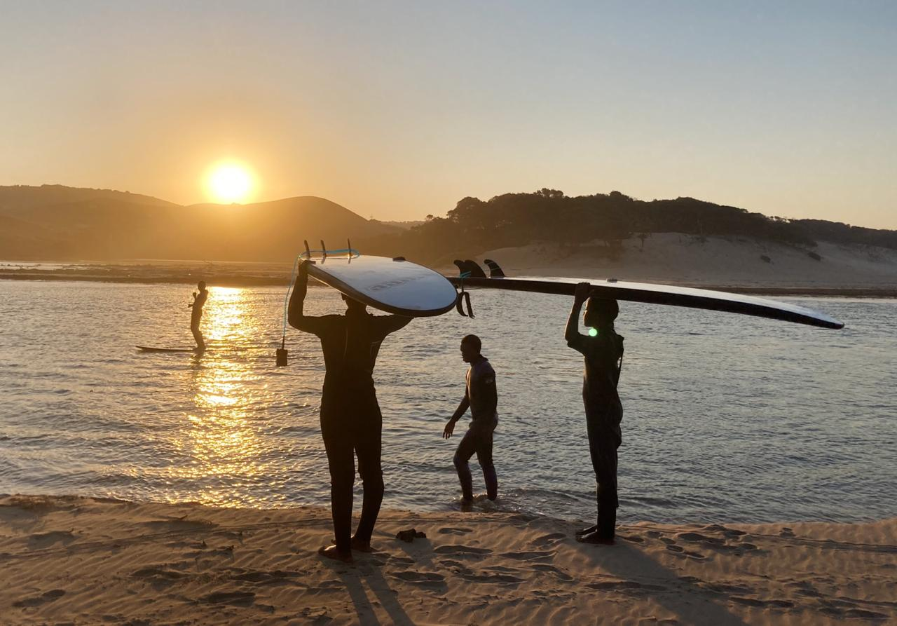 Three surfers watch a man standing on a surfboard and the sun set behind the dunes