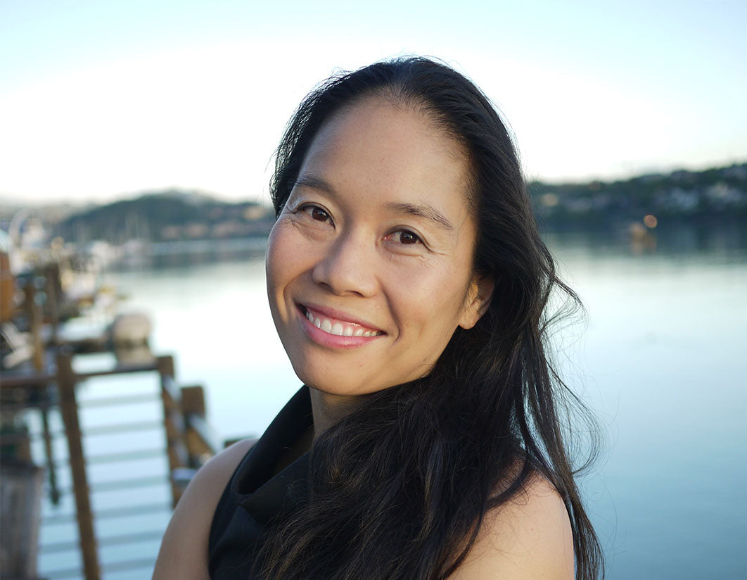 Bonnie Tsui, the author of Why We Swim standing in front of a lake