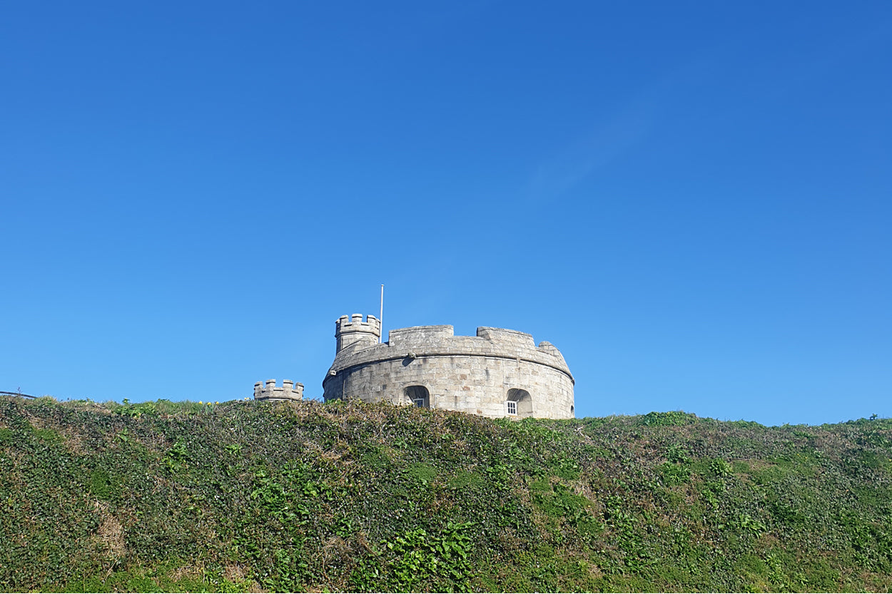 The top of Pendennis Castle peeks above the high moat that surrounds it.