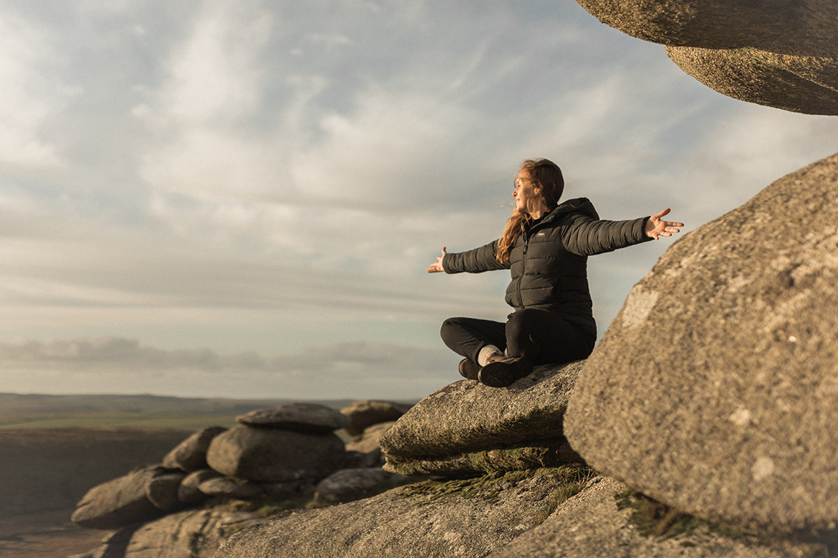Jen welcomes the sunset with open arms atop a rocky Cornish outcrop