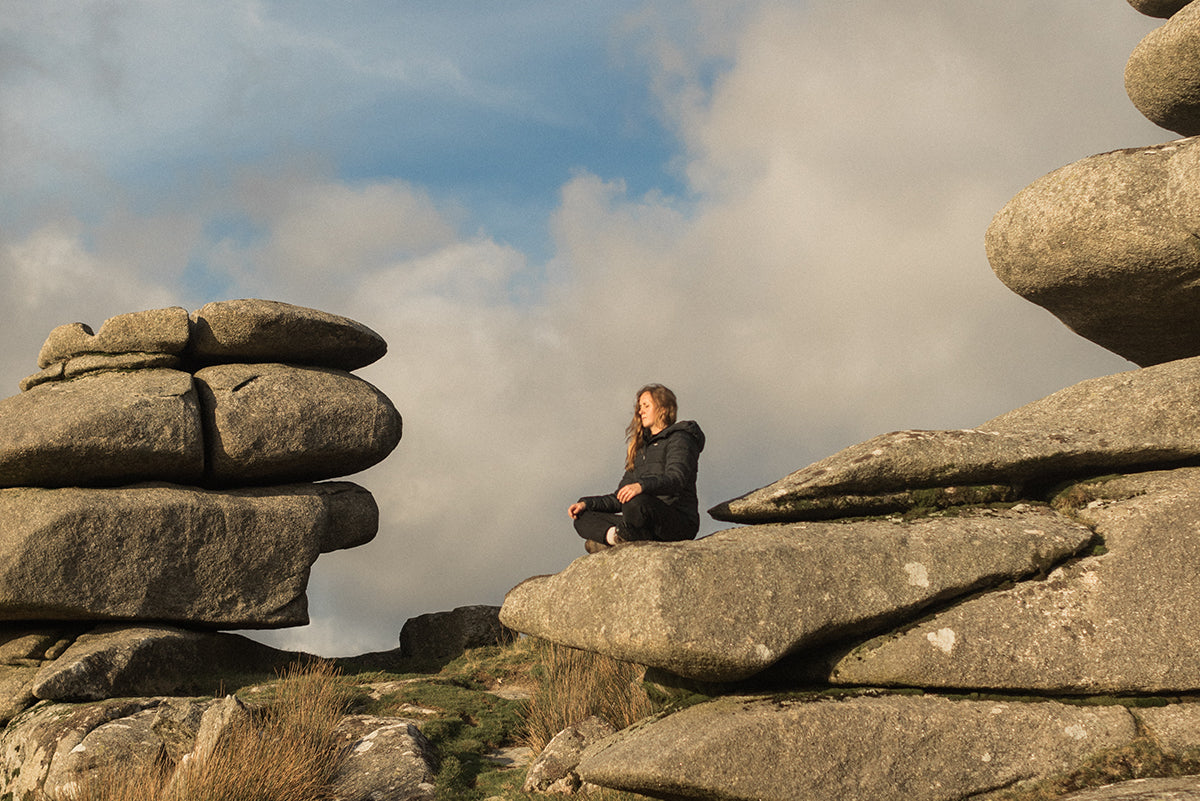 Jen Hannibal sits meditating on a rocky outcrop somewhere in Cornwall