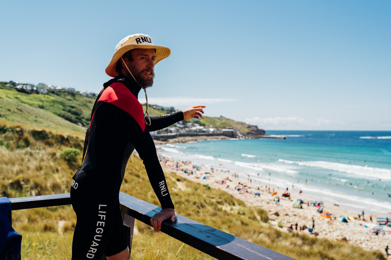Finisterre Ambassador Mike Lay stands watch at Sennen beach
