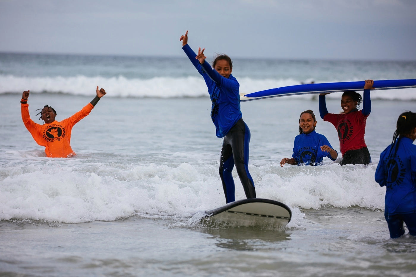 A young W4C participant is cheered onto a wave by the instructor
