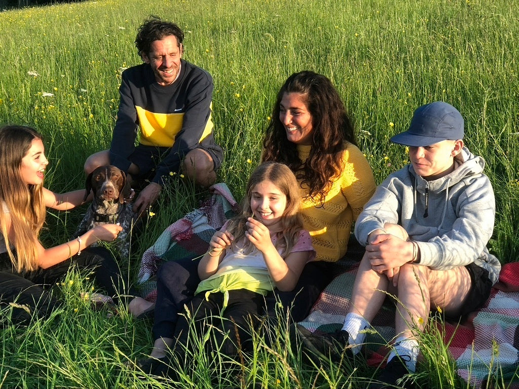 Dan and Seemah Burgess with their three children in a grassy meadow.