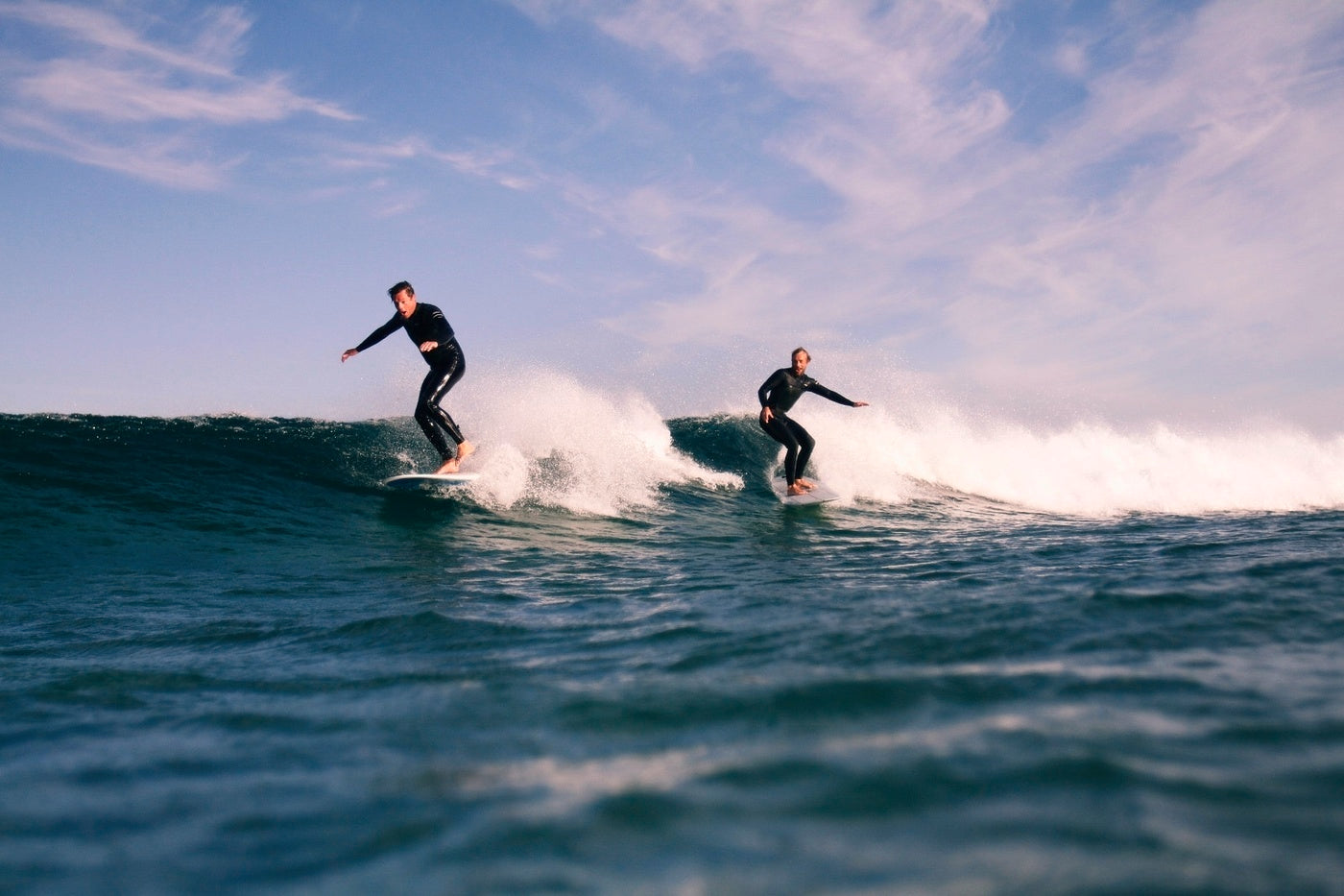 Surfers Sam Bleakley and Mike Lay share a wave under a blue Cornish sky