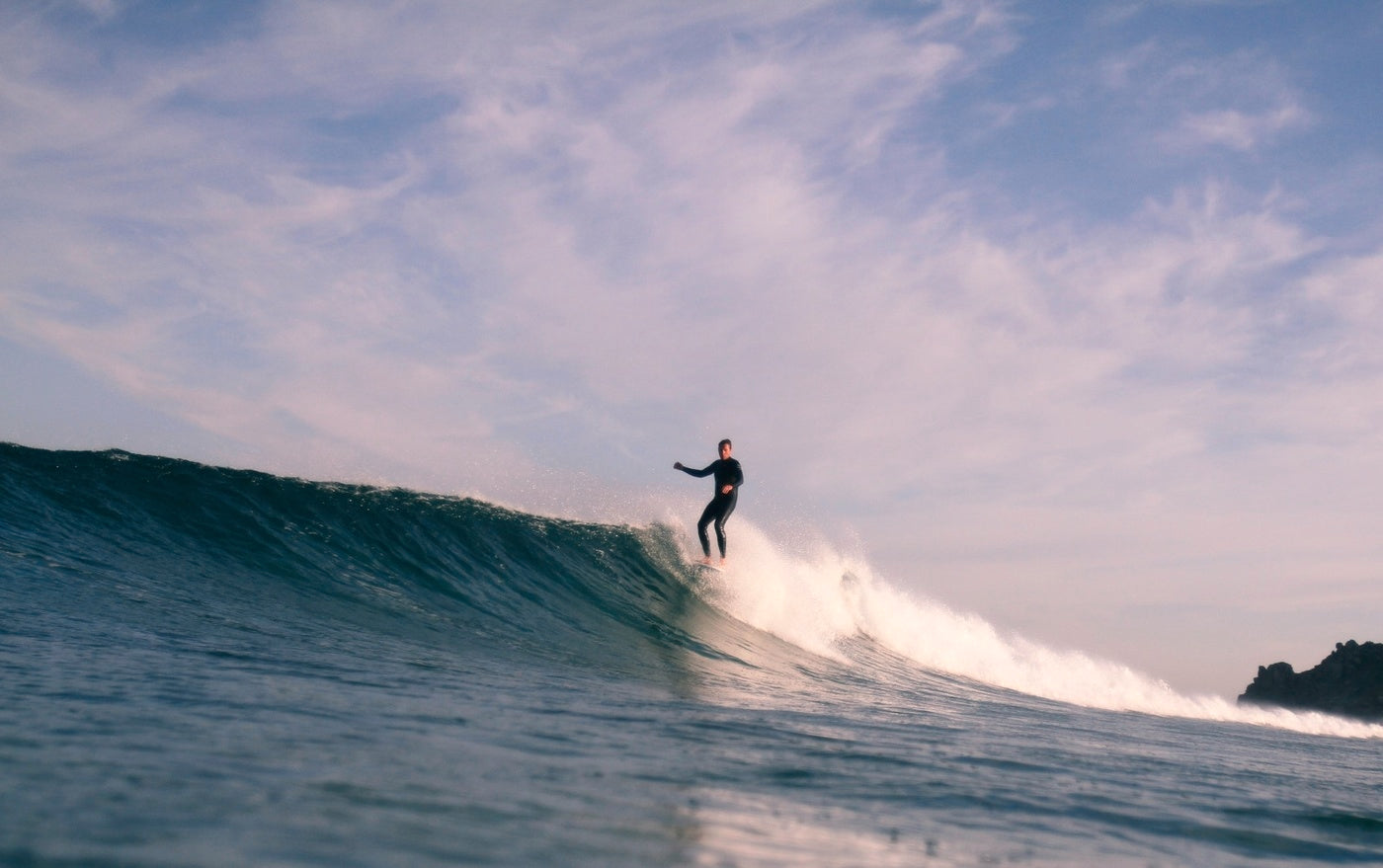 Sam Bleakley poised on the nose at the crest of a clean right hander in Cornwall