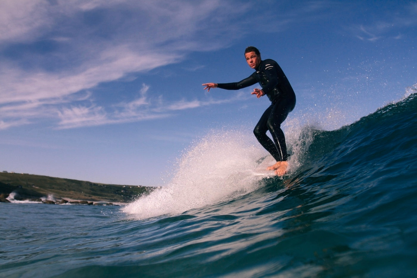 Sam Bleakley hanging five on the crest of a wave at his local break
