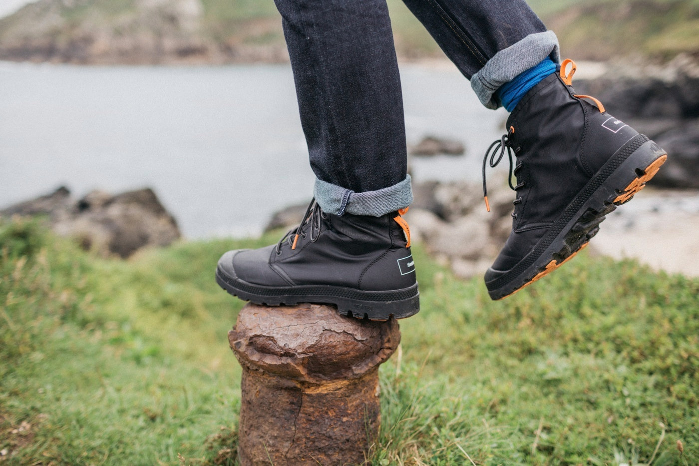 Someone wearing Palladium + Finisterre boots balancing on an iron mooring post