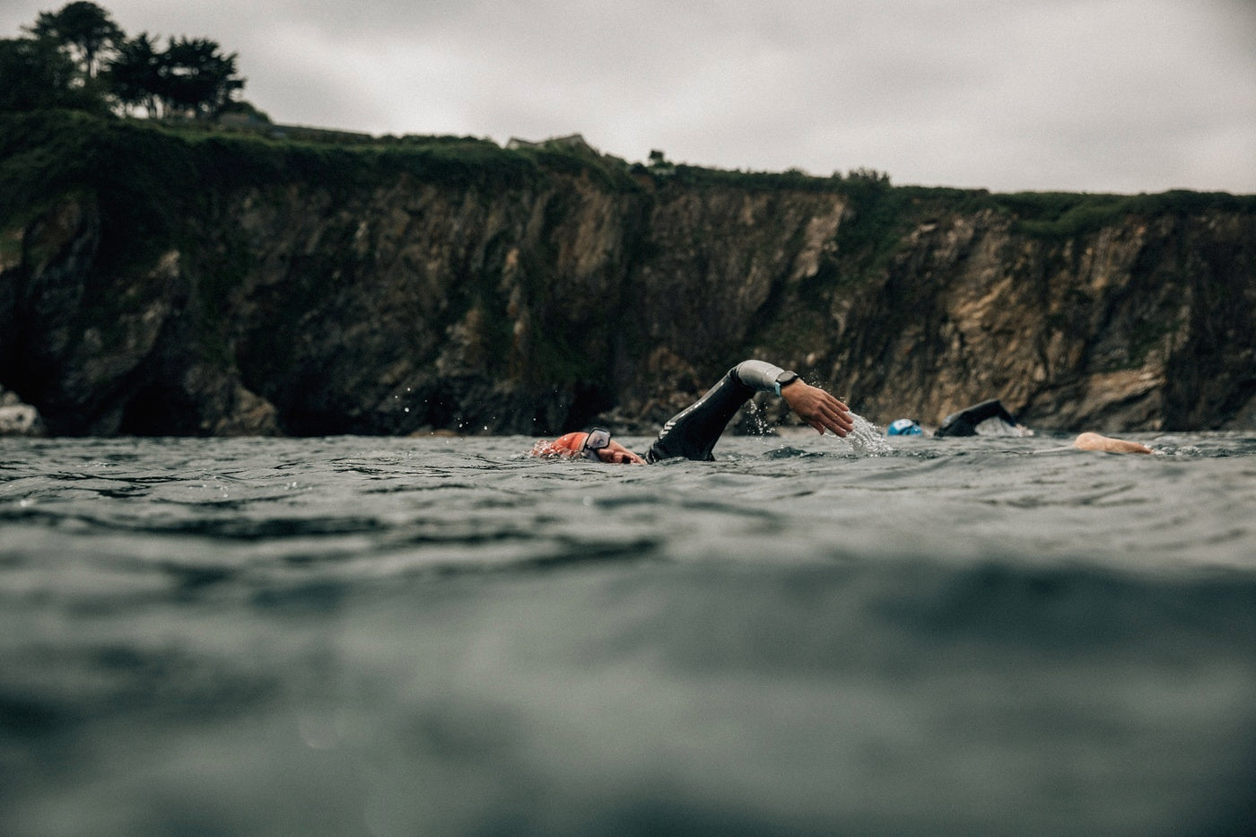 Outdoor Swimmers pictured swimming in the sea with a backdrop of Cornish cliffs