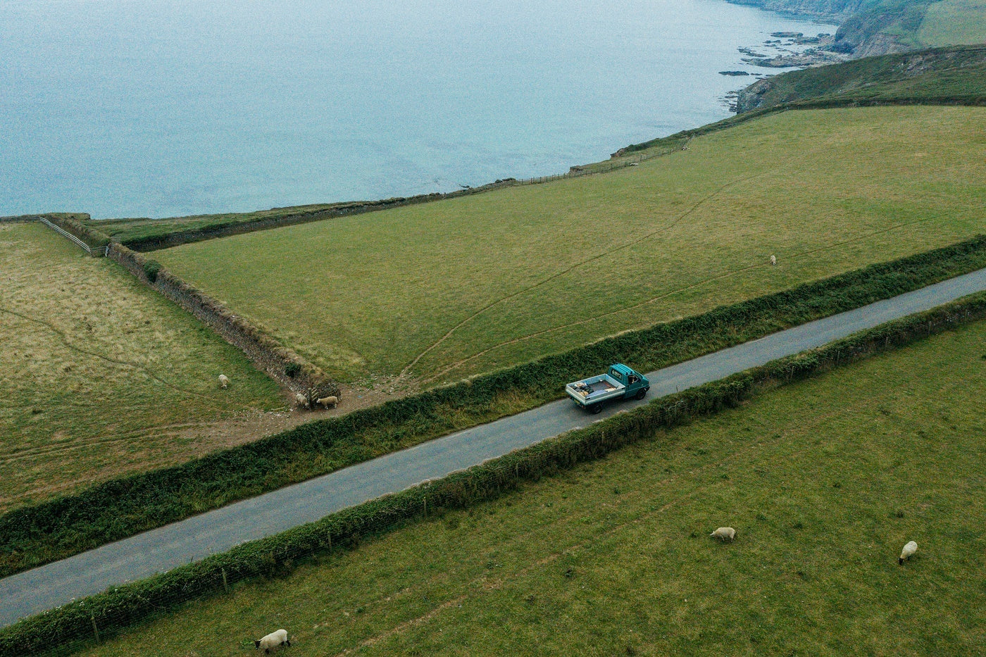 Our adventure van driving on the winding road above the sea.