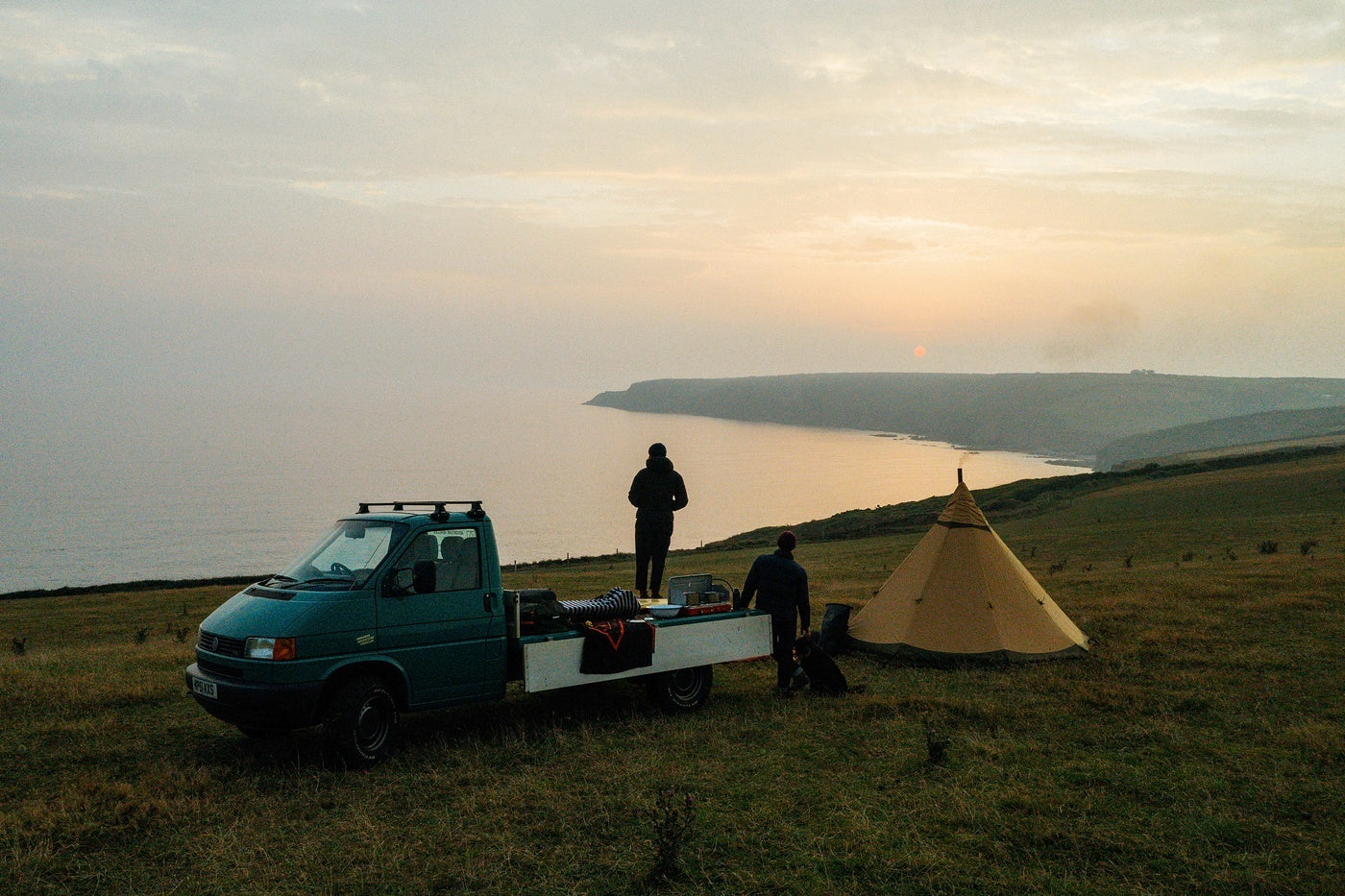 The crew watch the sun set into the sea from their camp for the night