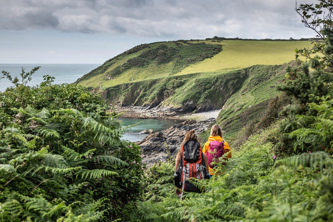The author and friends winding their way down a coastal trail to blue waters