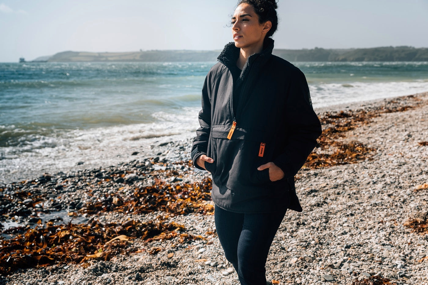 Woman wearing the Finisterre x Arkair smock in black, walking on a beach.
