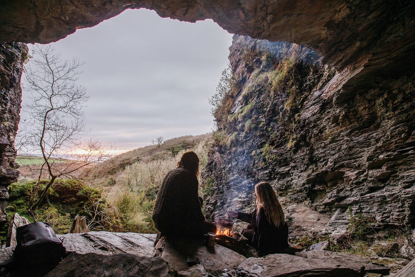 Man and woman set a campfire in a cave as the sun goes down