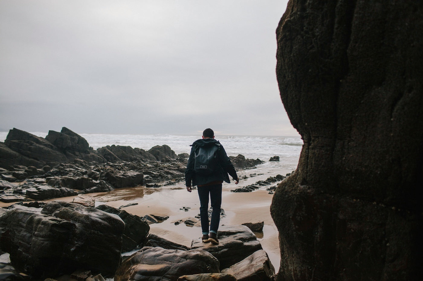 Man wearing the Finisterre stormbird jacket and drift backpack walks over a rocky shoreline