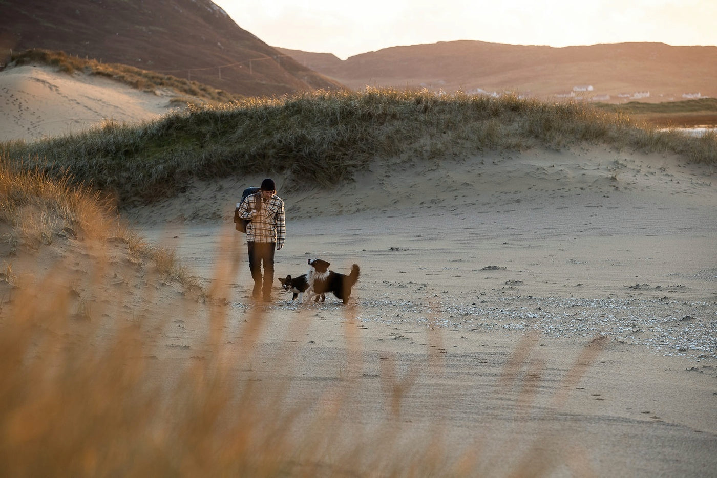 Colin Macleod with his dogs walking along a beach on the Isle of Lewis