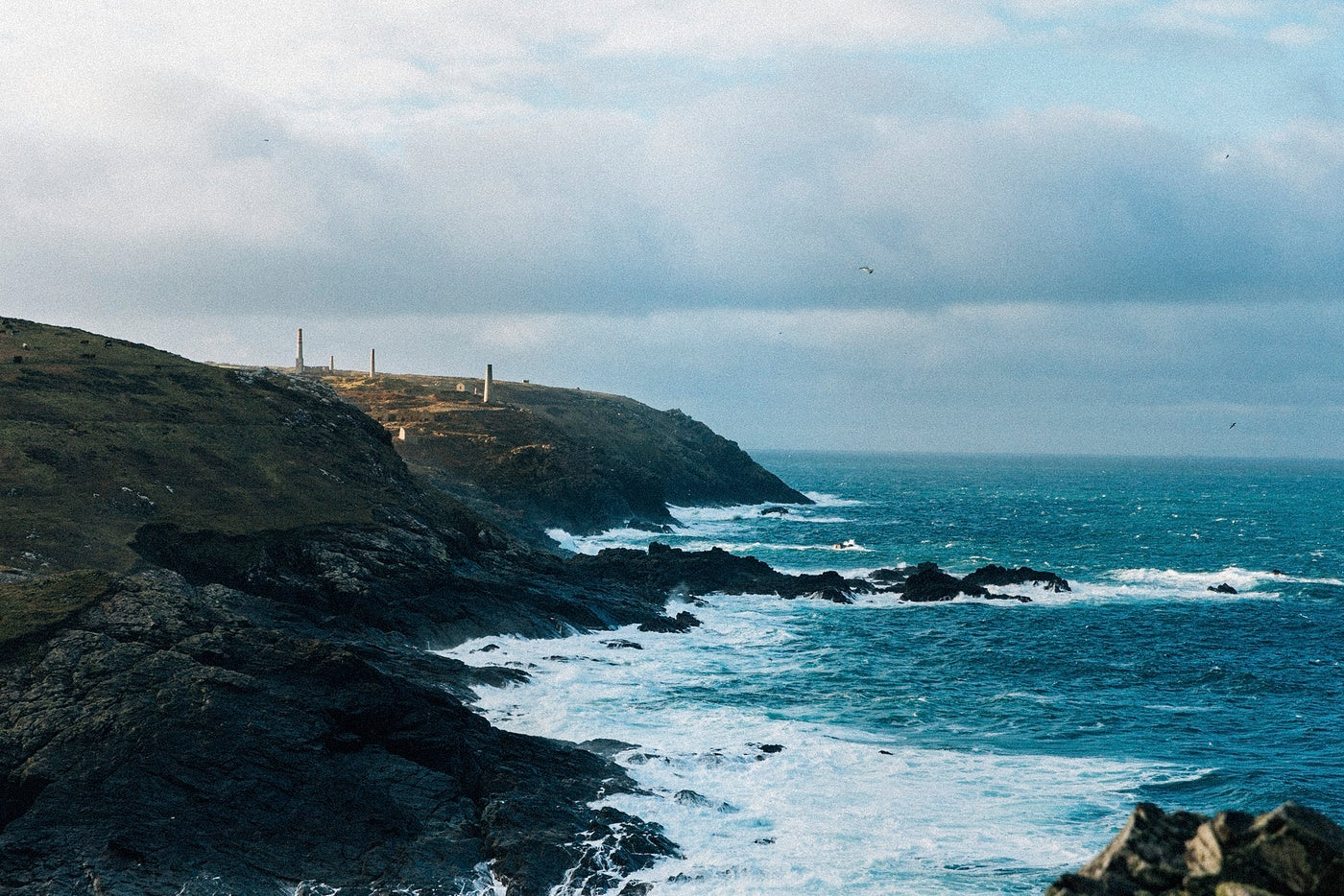 A windswept stretch of Cornish coastline, whitewater beating against the cliffs