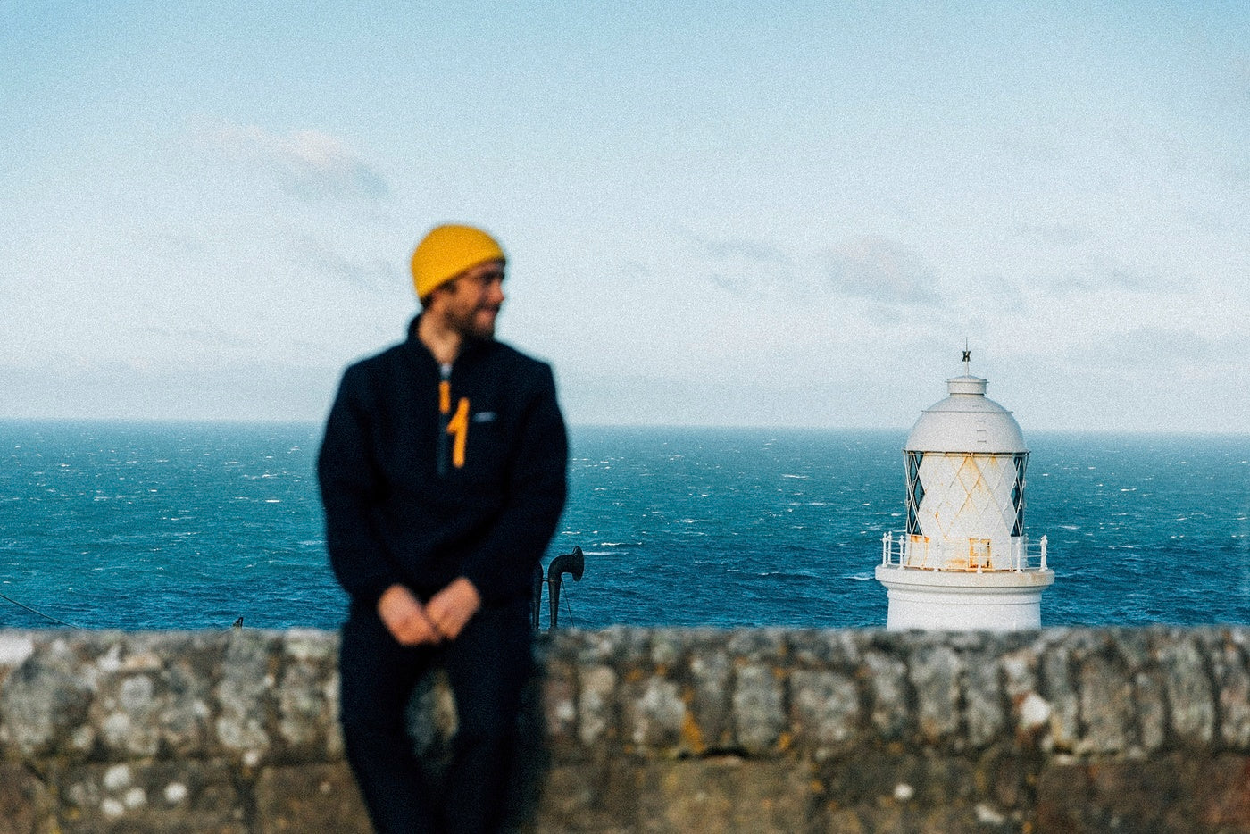 Mike Lay sits on a wall in front of a white lighthouse somewhere in West Cornwall