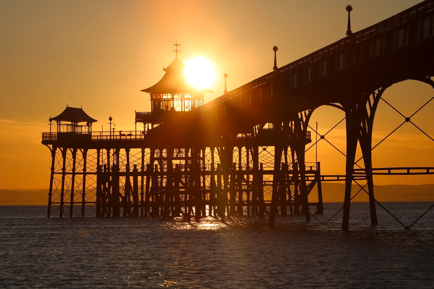 Clevedon Pier with a blazing sun setting behind it into the Bristol channel.