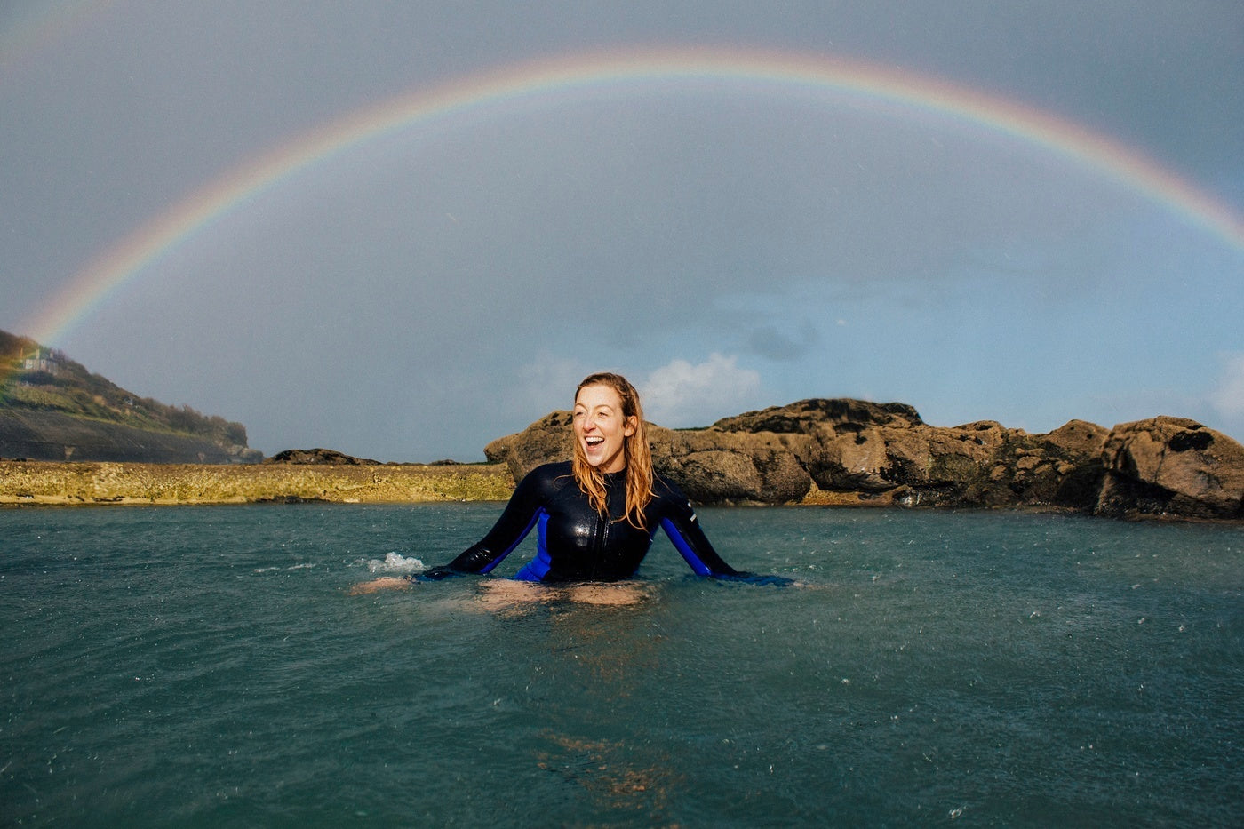 Our Wetsuit tester poppy sits under a rainbow in the local tidal pool