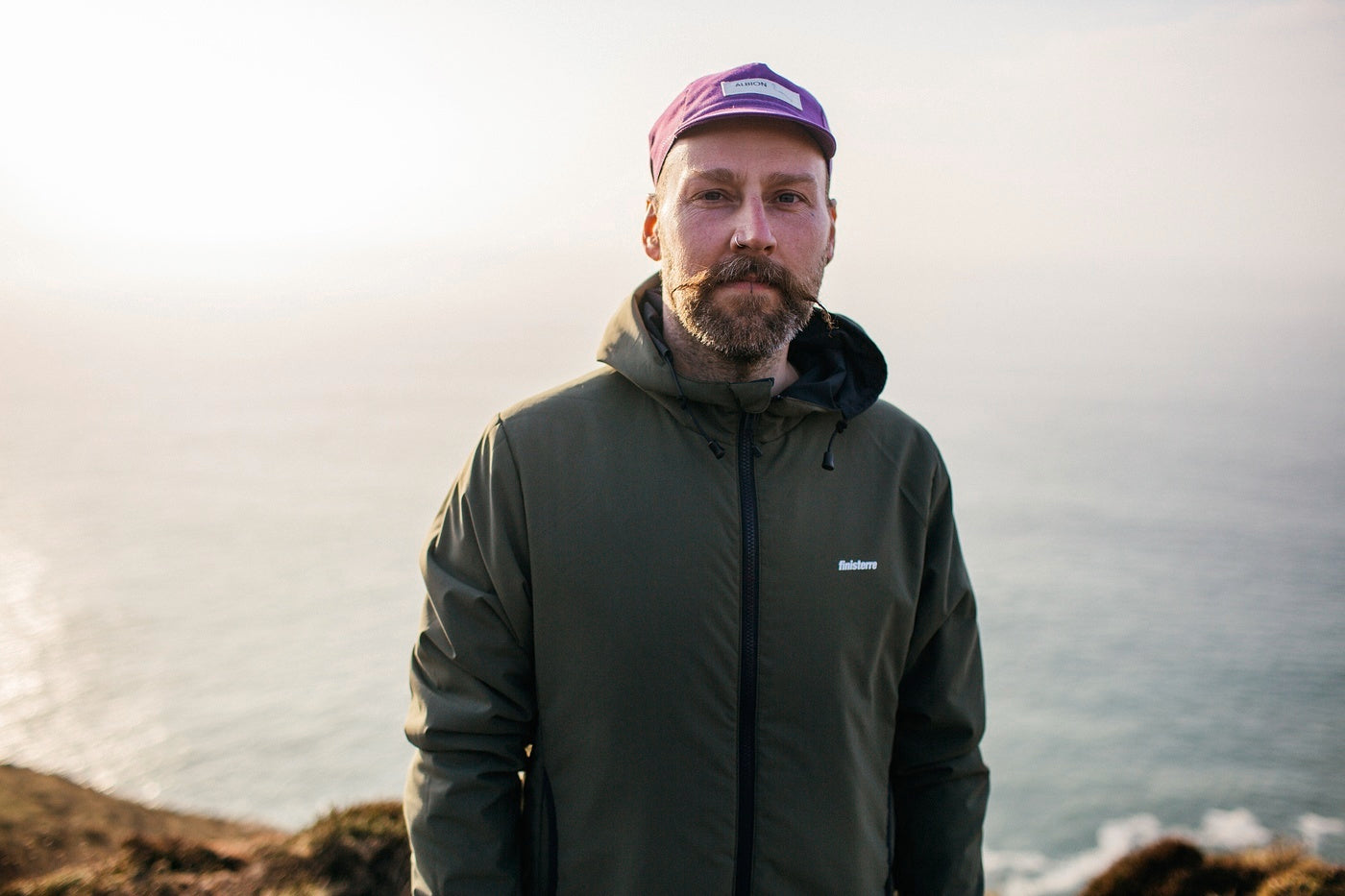 Finisterre Design Lead Todd stands on a cliff with the sea behind him