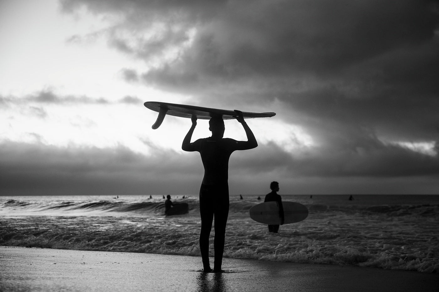A grey sky as Finisterre Ambassador Apish Tshetsha enters the water for a surf therapy session