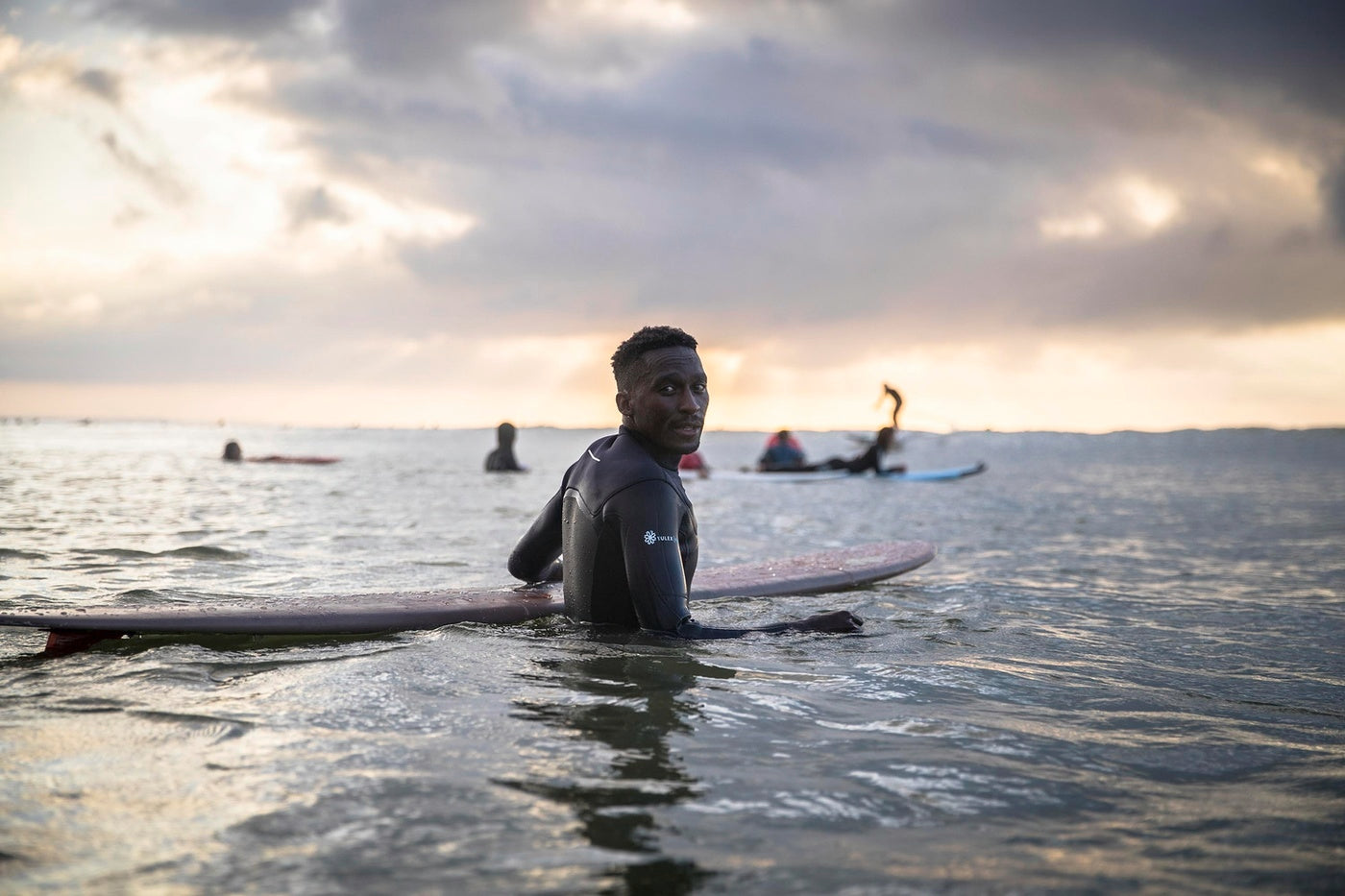 Finisterre Ambassador Apish Tshetsha in the water for a surf therapy session
