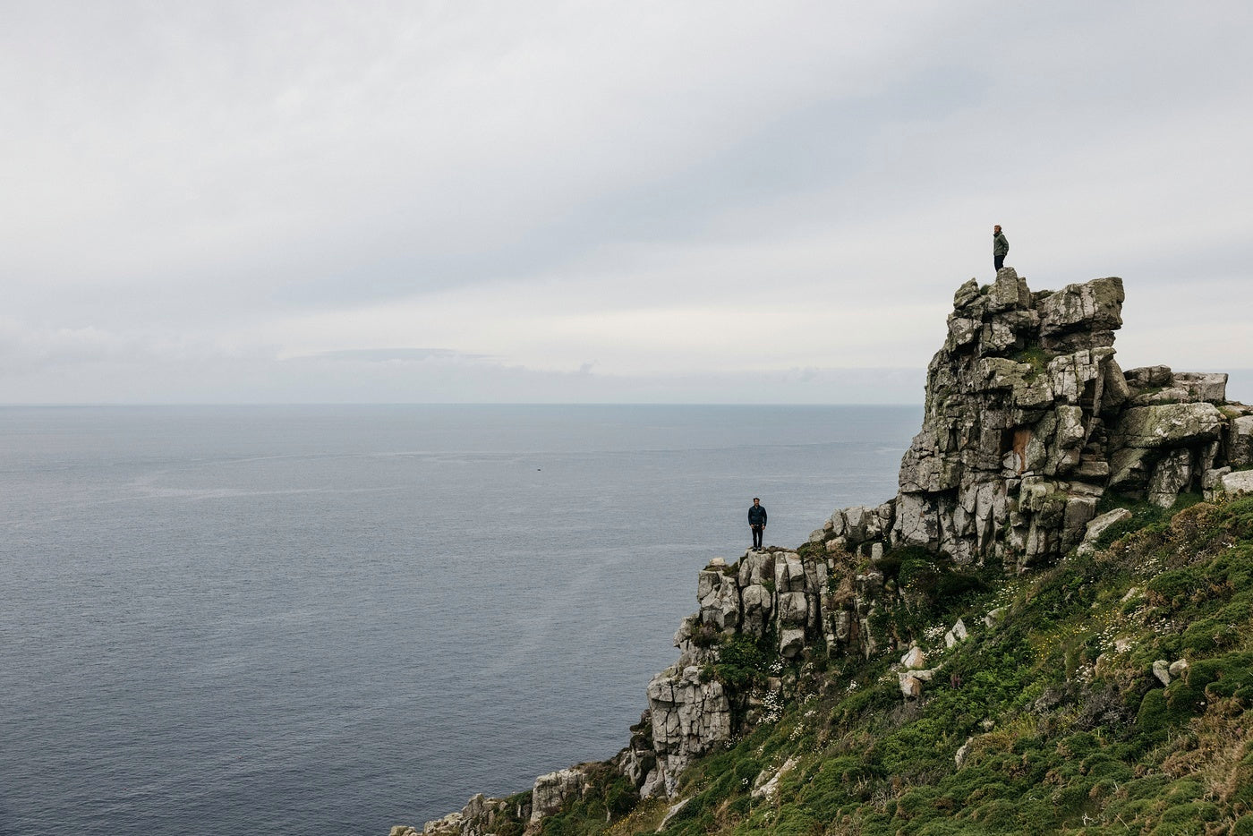 Two silhouettes stand on a rocky Cornish outcrop above the sea