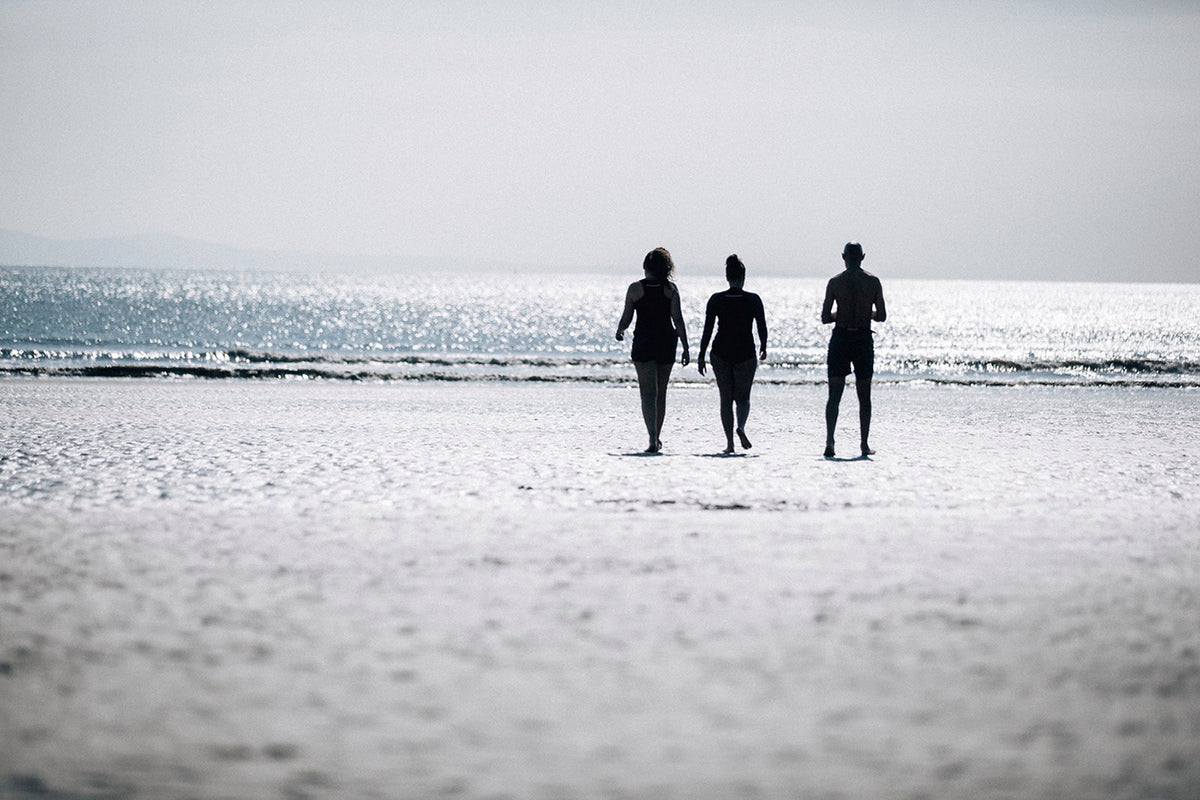 Silhouettes of Omie, Phil and Soraya heading to the water for a swim