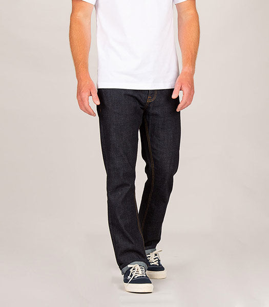 Front of mans legs wearing indigo straight fit organic cotton denim jeans by Finisterre