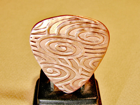 Copper guitar pick for swirling waves of sound