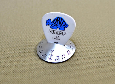 Aluminum guitar pick stand disc shaped with musical inspiration