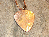 Copper guitar pick necklace with swirling waves of sound