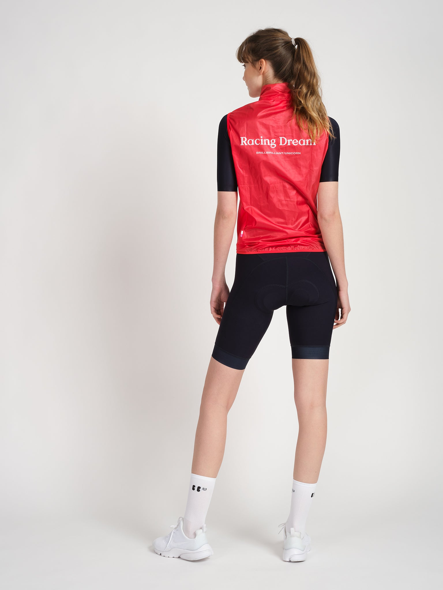 Female model facing backward wearing RD jersey in purple and RD Gilet in red, featuring white Racing Dream logo.