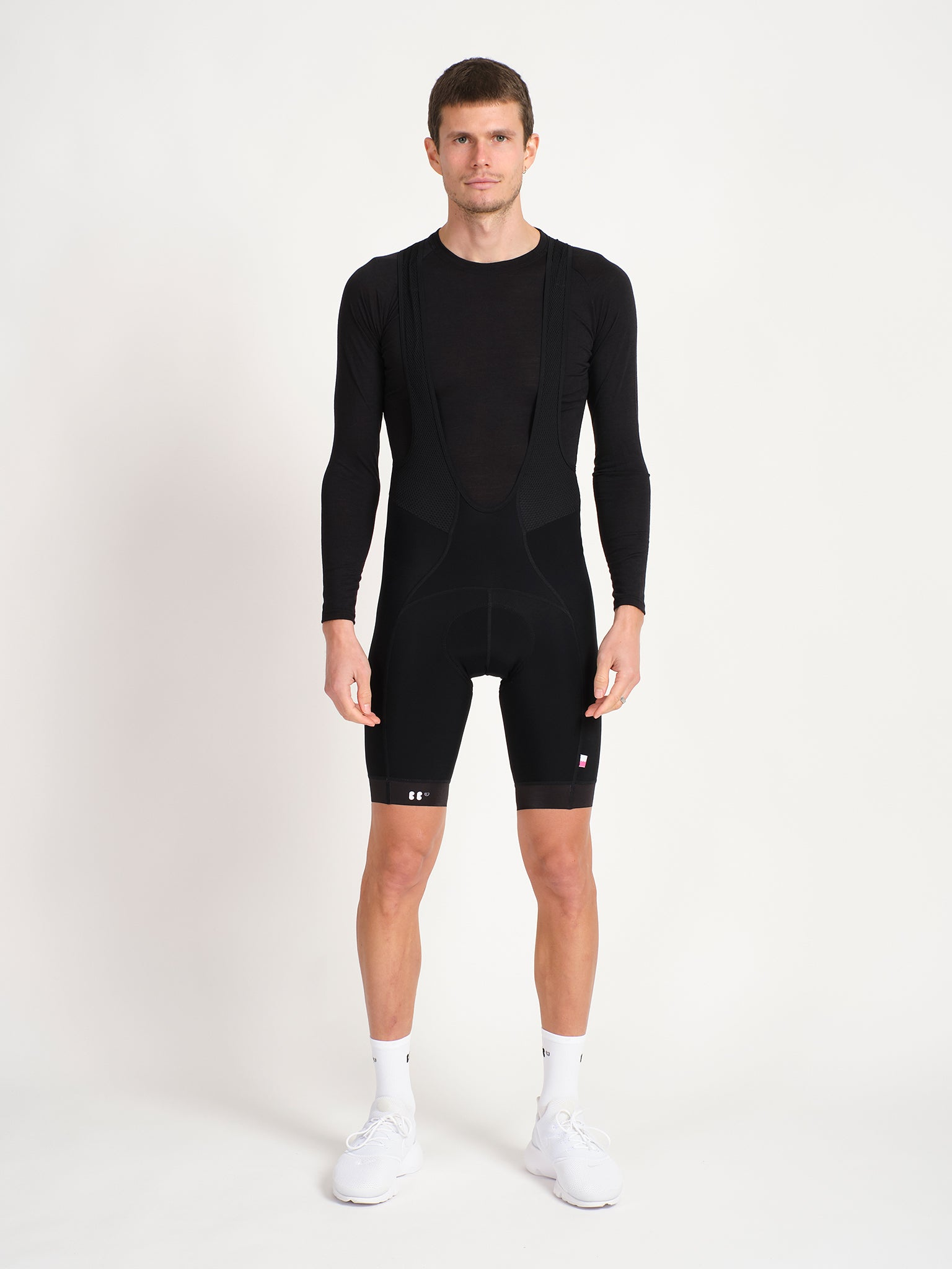 Male model facing forward wearing black merino baselayer.