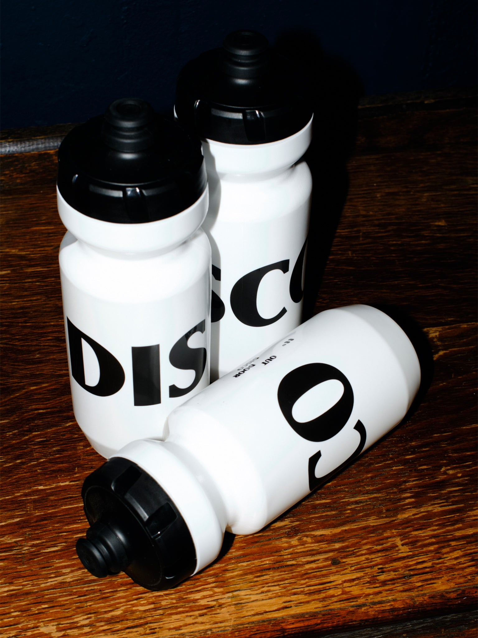 Three white bidons with a black DISCO logo.