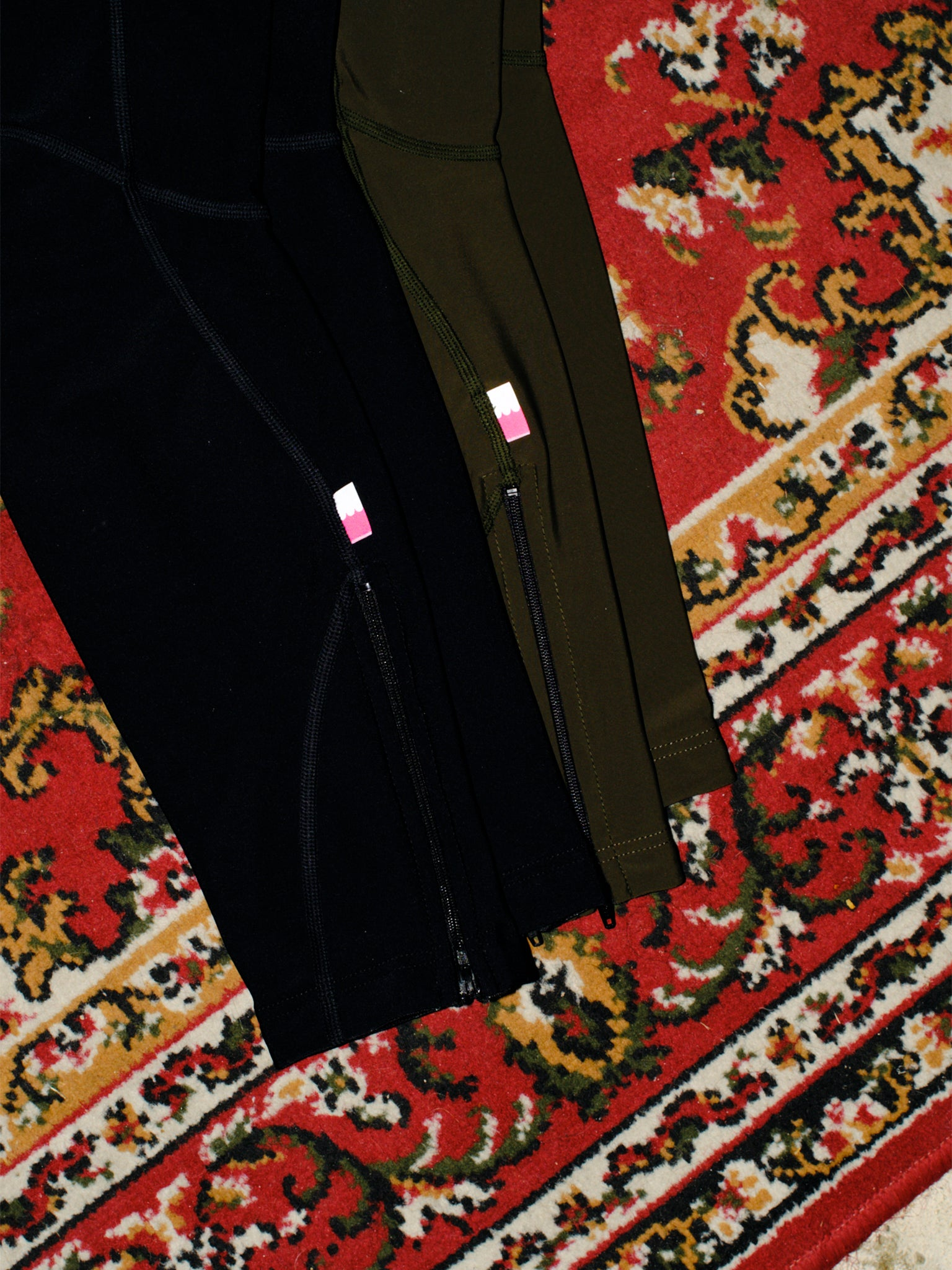 Black and olive Everyday Pro Legwarmers on a patterned carpet