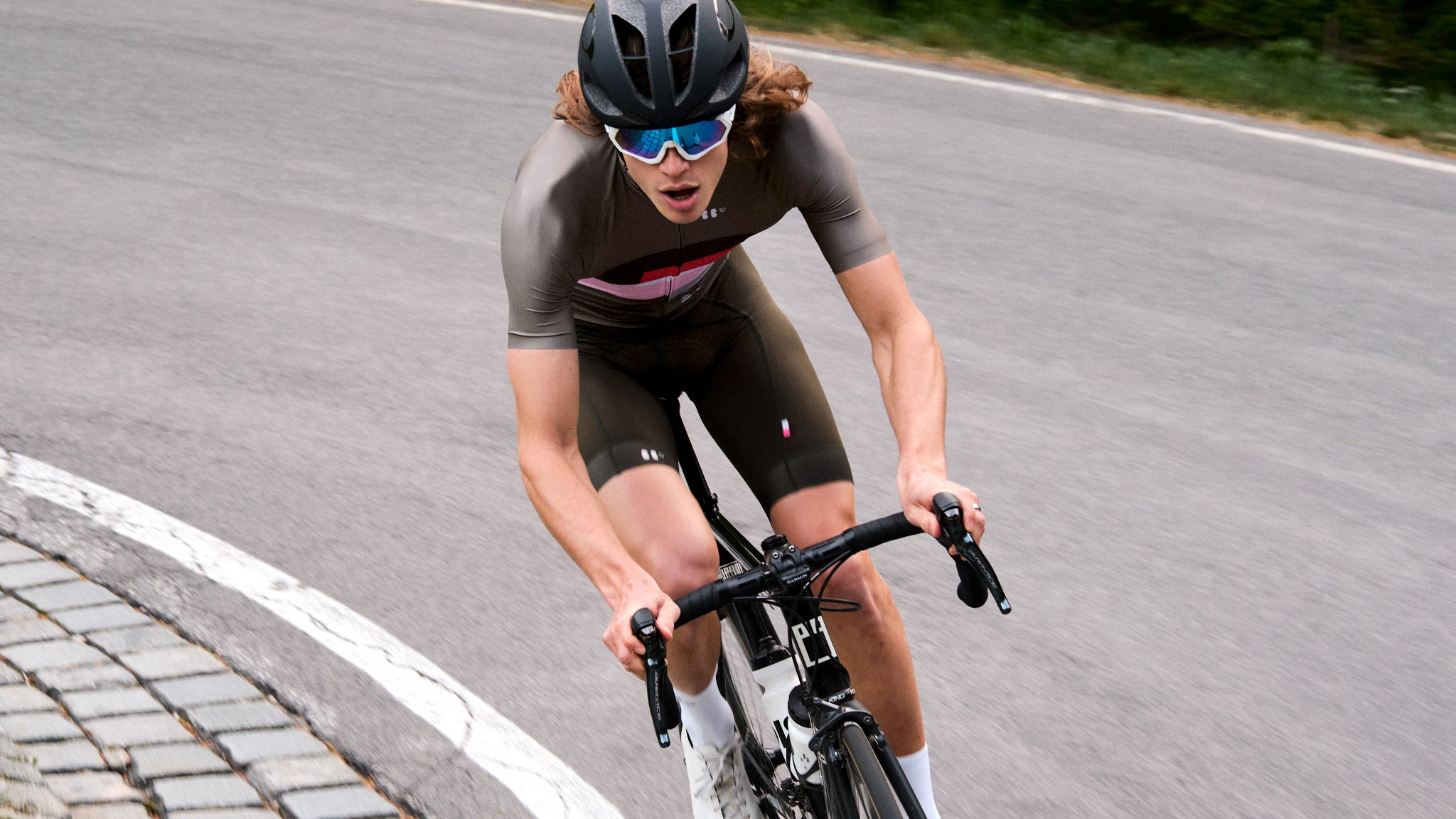 A rider climbing through a hairpin, brething with his mouth open and wearing the FNC jersey in olive and matching Dance bibs in olive.