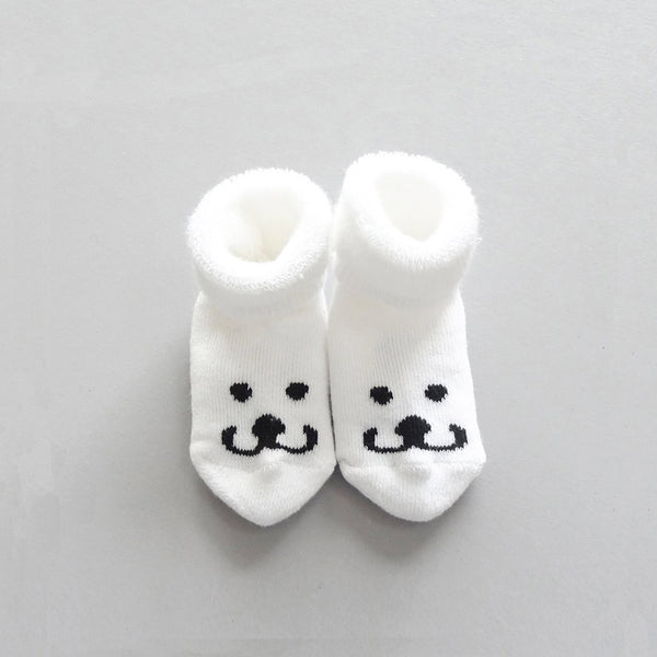 Soft, white baby booties the Smile of Brom