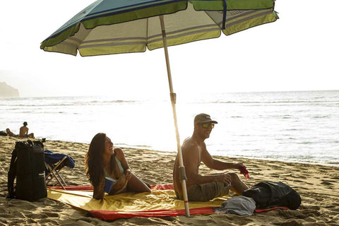 couple sitting on the beach using the parasheet beach blanket