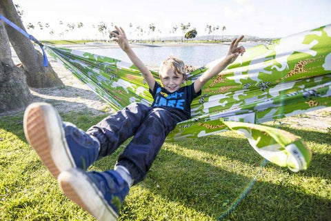 young boy sitting in a green hammock with his arms up, excited