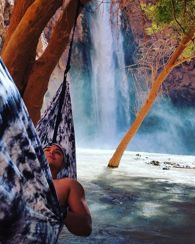 man hammocking in front of a waterfall in Havasupai